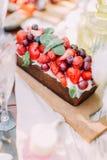 La photo latérale légère du gâteau mousseline savoureux de chocolade décoré des fraises et des cerises juteuses Photographie stock