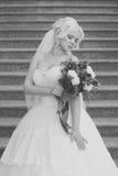 La photo noire et blanche de la jeune mariée avec un bouquet fleurit Photos stock