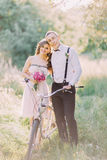 La photo verticale des bridesmais et du meilleur homme étreignant, tenant le bouquet rose et la bicyclette au printemps images stock