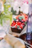 La photo verticale du gâteau de fruit d'éponge de chocolade décoré des baies rouges telles que les cerises et les fraises juteuse Photo libre de droits