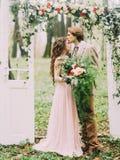 La photo verticale en gros plan du marié dans le costume de vintage embrassant sa jeune mariée avec le grand bouquet dans le fron Image stock