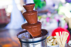 La photo vibrante de la fontaine Fontain de chocolat sur des enfants badine la fête d'anniversaire avec des enfants jouant autour Images stock
