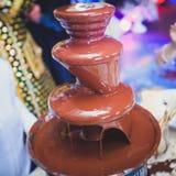 La photo vibrante de la fontaine Fontain de chocolat sur des enfants badine la fête d'anniversaire avec des enfants jouant autour Image stock