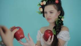 La photographe de femme travaille avec le jeune modèle d'une façon de ressort avec le fruit dans le studio Tir des coulisses pend banque de vidéos