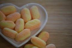 La photographie de nourriture pour des valentines avec le plat blanc de forme de coeur d'amour a rempli de bonbons à sucre de suc Photographie stock
