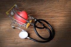 La photographie de peinture de la vie avec le stéthoscope et le coeur toujours rouge forment sur de mini caddies remplis de coeur Photographie stock