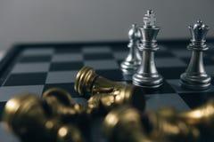 La pièce d'échecs de roi avec des échecs d'autres tout près vont vers le bas du concept de flottement de jeu de société des affai Images stock