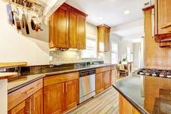 La pièce de cuisine avec les dessus noirs de granit et le dos de tuile éclaboussent l'équilibre Photos libres de droits