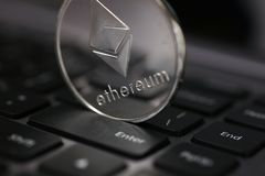 La pièce de monnaie argentée d'ethereum se trouve sur l'ordinateur portable photographie stock