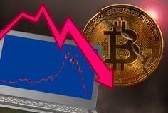 La pièce de monnaie de Bitcoin a fendu dans l'accident du marché avec le graphique d'ordinateur portable images libres de droits