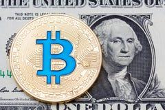 La pièce de monnaie bleue d'or de bitcoin sur des dollars US se ferment  Images stock