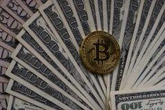 La pièce de monnaie d'or de bitcoin sur des dollars US se ferment  images stock