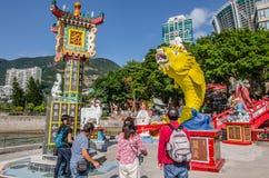 La pièce de monnaie de jet de personnes à de grands poissons jaunes de bouche croient le temple chanceux de yin de Kuan Photo stock