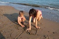 La pièce de soeurs sur la plage. Images libres de droits