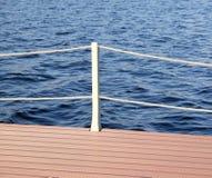 La pièce du quai et la clôture avec des cordes de la surface de l'eau Images stock