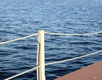 La pièce du quai et la clôture avec des cordes de la surface de l'eau Photographie stock libre de droits