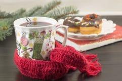 La pièce en t dans un decoupage a décoré la tasse de thé et les butées toriques de Noël Image stock