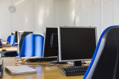 La pièce informatique avec le bleu préside des moniteurs d'un PC Images stock