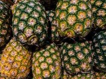 La piña fresca con verde y el amarillo raspan en cesta en el mercado Fotografía de archivo libre de regalías