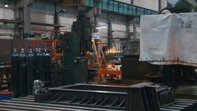 La pianta - bombole a gas per le costruzioni del metallo e della saldatura - nella distanza un uomo lavora ad un cercular stock footage