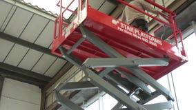 La piattaforma elevatrice idraulica di forbici aumenta in un magazzino video d archivio