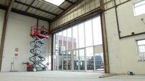 La piattaforma elevatrice idraulica di forbici aumenta in un magazzino archivi video