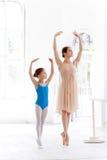 La piccola ballerina che posa alla sbarra di balletto con l'insegnante personale nello studio di ballo Fotografia Stock