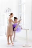 La piccola ballerina che posa alla sbarra di balletto con l'insegnante personale nello studio di ballo immagine stock