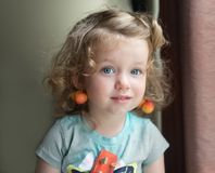 La piccola bambino-ragazza caucasica bionda adorabile dei capelli ricci con gli occhi azzurri e con una ciliegia come orecchini s fotografia stock