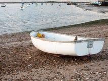 La piccola barca privata bianca parcheggiata ha attraccato sulla baia della parte anteriore della spiaggia Immagini Stock