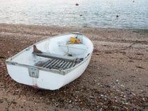La piccola barca privata bianca parcheggiata ha attraccato sulla baia della parte anteriore della spiaggia Fotografie Stock Libere da Diritti