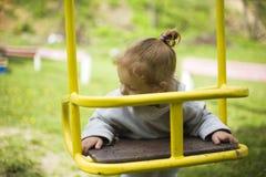 La piccola bella ragazza dai capelli rossi ha appeso su un'oscillazione, bambino gioca su un'oscillazione sul campo da giuoco fotografia stock libera da diritti