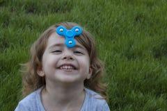 La piccola bella ragazza del ritratto sta giocando il filatore blu Fotografia Stock