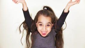 La piccola bella ragazza dolce è felice, sorridendo, rallegrantesi, alza le sue armi alla cima, fondo sorpreso e bianco, bianco video d archivio