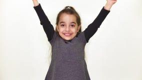 La piccola bella ragazza dolce è felice, sorridendo, rallegrantesi, alza le sue armi alla cima, fondo sorpreso e bianco, bianco archivi video