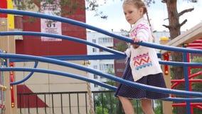 La piccola bella ragazza gioca sul campo da giuoco dei bambini nel giorno di estate archivi video