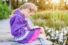 La piccola bella ragazza ha letto i libri elettronici Fotografia Stock Libera da Diritti