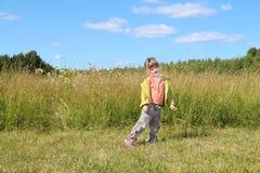 La piccola bella ragazza posa vicino ad erba alta al prato verde Immagine Stock Libera da Diritti