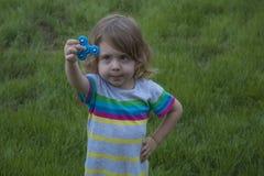 La piccola bella ragazza sta giocando il filatore blu a disposizione Fotografia Stock