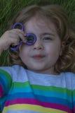 La piccola bella ragazza sta giocando il filatore blu a disposizione Immagini Stock Libere da Diritti