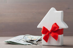 La piccola casa bianca ha decorato il nastro rosso dell'arco con il mazzo di chiavi e di denaro contante sulla tavola di legno Re Fotografie Stock Libere da Diritti