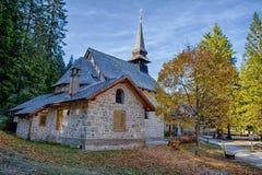La piccola chiesa nel lago Braies nel tempo di autunno, in alpi delle dolomia, valle italiane di Pusteria, dentro il Fanes - il S immagine stock