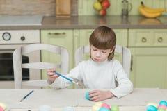 La piccola coloritura bionda del ragazzo del bambino eggs per la festa di Pasqua in cucina domestica Immagini Stock Libere da Diritti