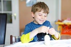 La piccola coloritura bionda del ragazzo del bambino eggs per la festa di Pasqua in cucina domestica, all'interno Immagine Stock