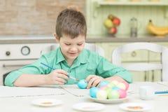 La piccola coloritura bionda del ragazzo del bambino eggs per la festa di Pasqua in cucina domestica Fotografia Stock