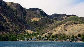 La piccola configurazione delle case del villaggio alla spiaggia sul piede di una montagna ha riempito di vegetazione verde Fotografia Stock Libera da Diritti