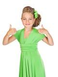 La piccola damigella d'onore con bei capelli in un vestito verde mostra i ges Fotografia Stock