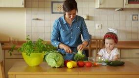 La piccola figlia aiuta sua madre a cucinare Hanno tagliato i broccoli Minestra vegetariana Stile di vita sano Famiglia vegetaria video d archivio