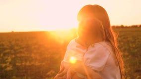 La piccola figlia cade addormentato in armi di sua madre nei bei raggi del sole Famiglia felice che cammina al tramonto nel parco video d archivio