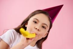 La piccola figlia in cappello del partito soffia nel ventilatore del partito immagine stock libera da diritti